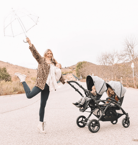 woman baby wearing, holding an umbrella and pushing a double stroller