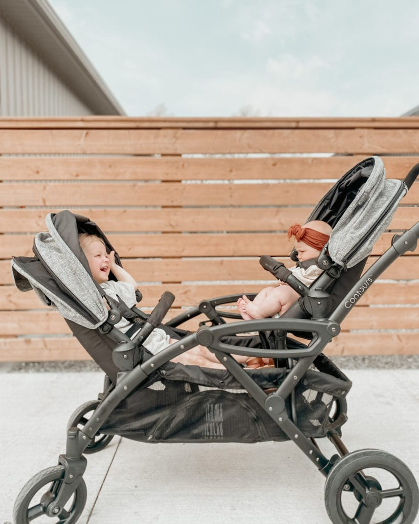 baby and child in a double stroller facing each other