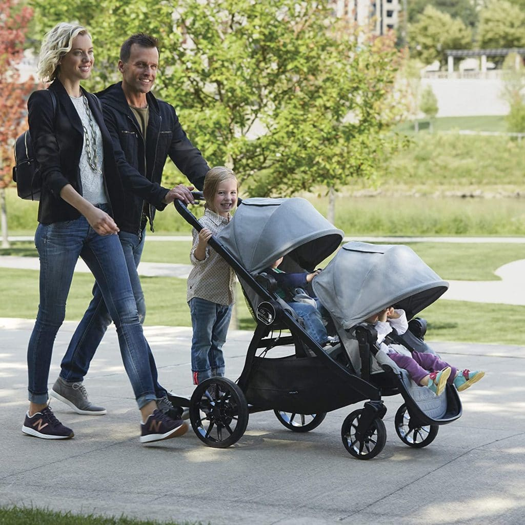 a couple with 3 children pushing a stroller