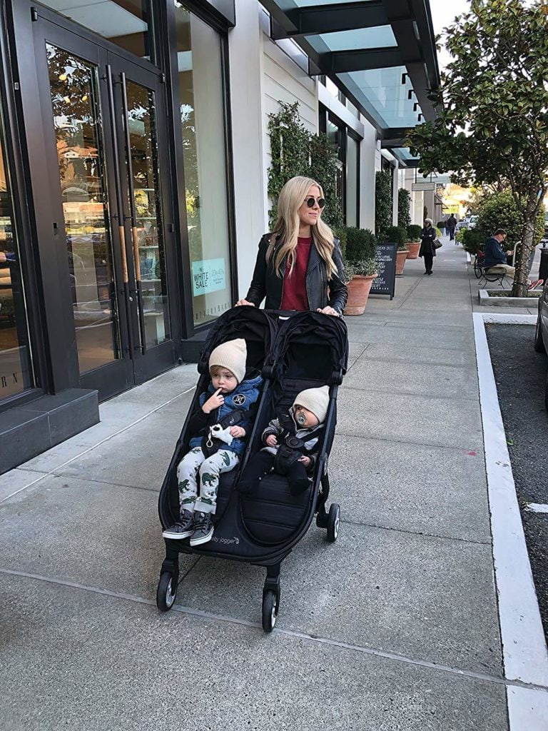 woman pushing the Baby Jogger City Tour 2 Double stroller with 2 kids in it