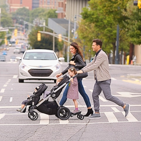 a couple with 3 children crossing the street with the Baby Jogger City Select Double Stroller and glider board attachment
