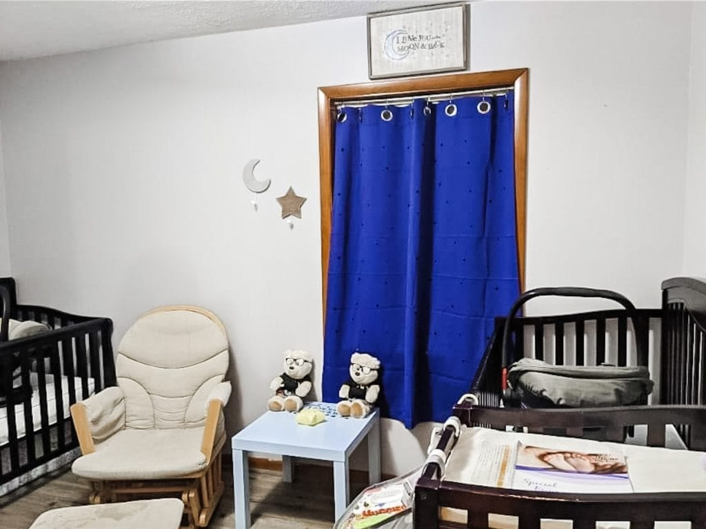 a twin nursery with a blue curtain and two cribs plus a glider and small table