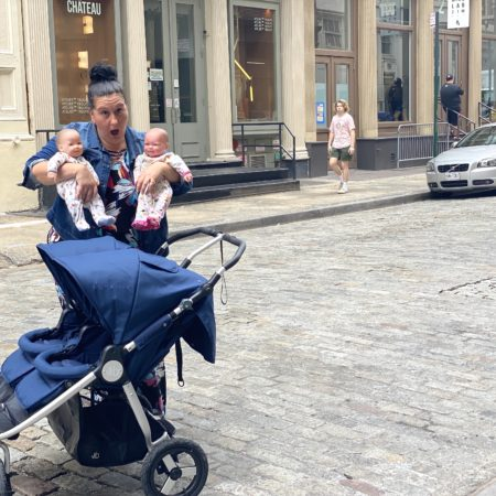 bumbleride indie twin stroller on the streets of new york city with a woman hold two baby dolls