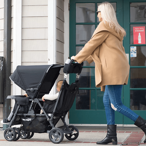 a woman pushing a tandem stroller with two kids on a sidewalk