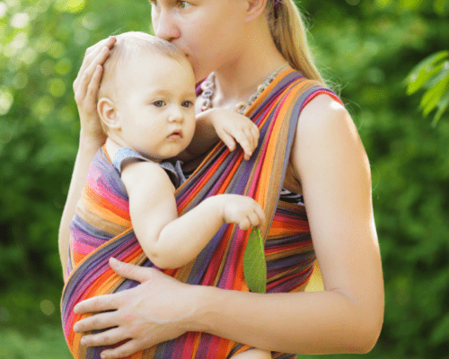 mom holding baby in a wrap carrier