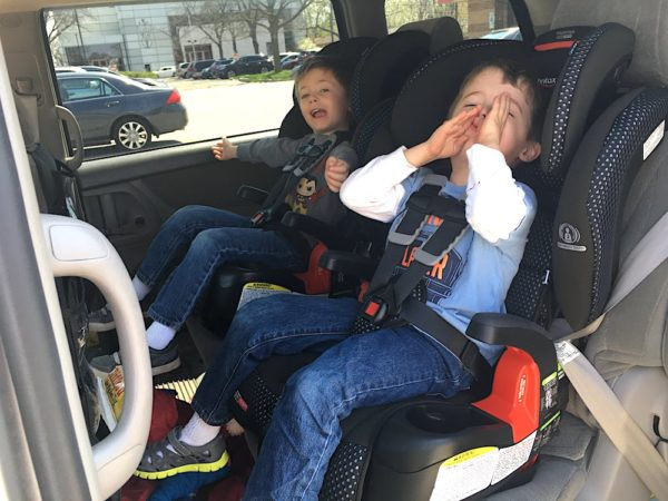 twin boys sitting in harness to booster car seats in a minivan