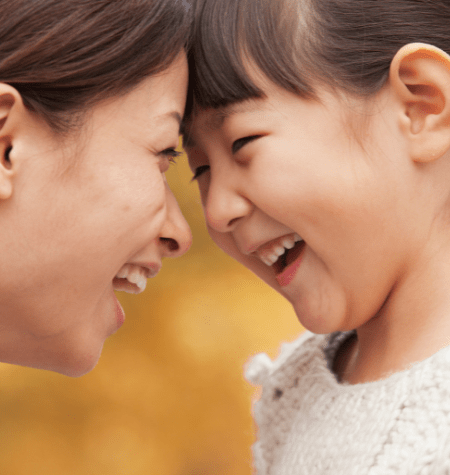 mom and girl faces smiling at each other