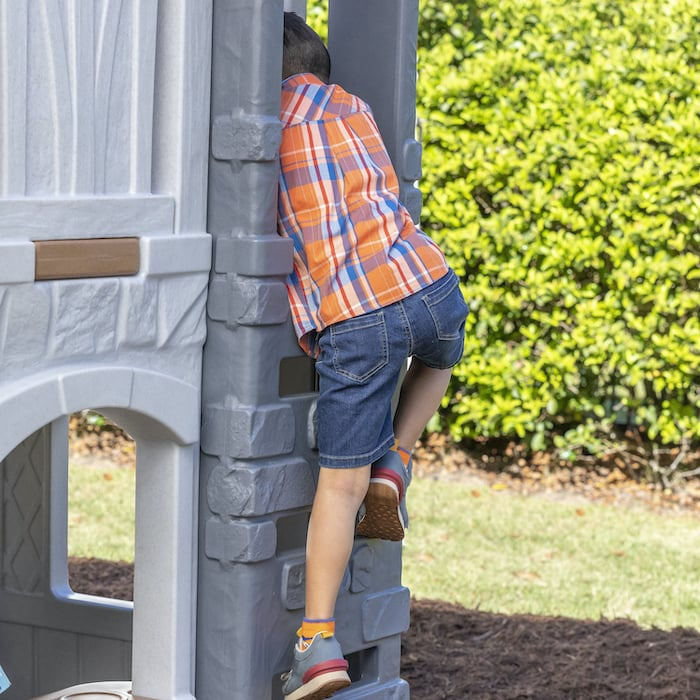boy climbing the ladder of a 2-story playhouse by step2