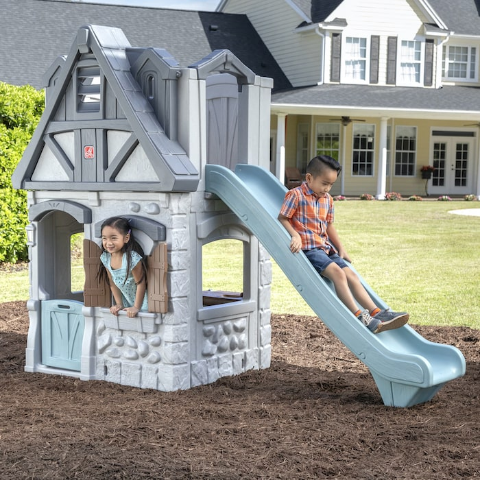 kids playing on a 2-story playhouse by step2