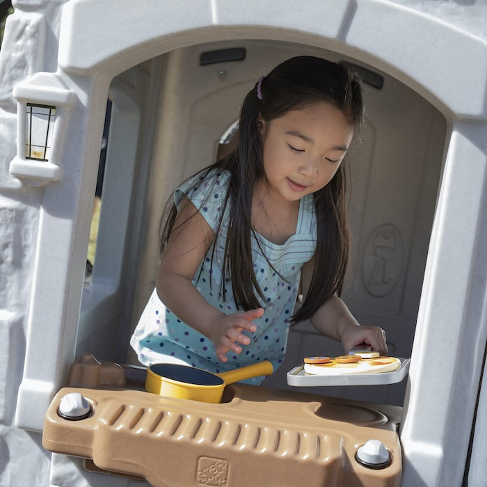 little girl playing in the play kitchen of a playhouse