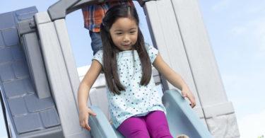 girl sliding down a slide on a playhouse Step2