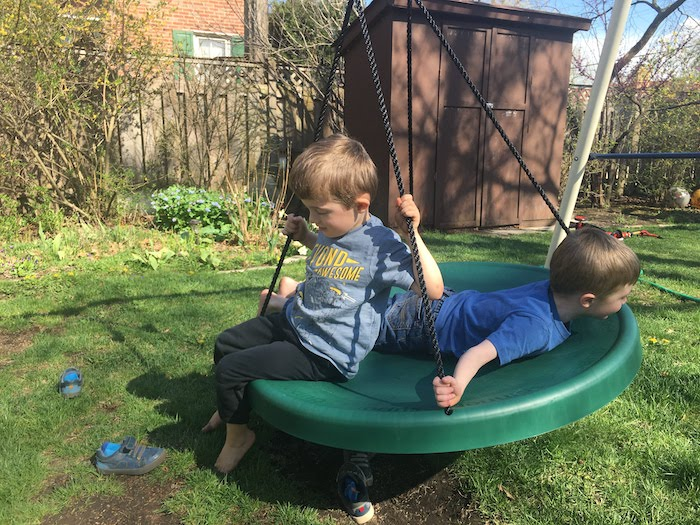 two boys on a spinning disc on a swing set in a backyard