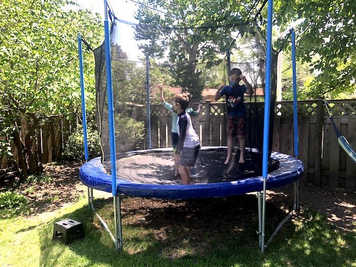 three boys jumping in a trampoline in a backyard