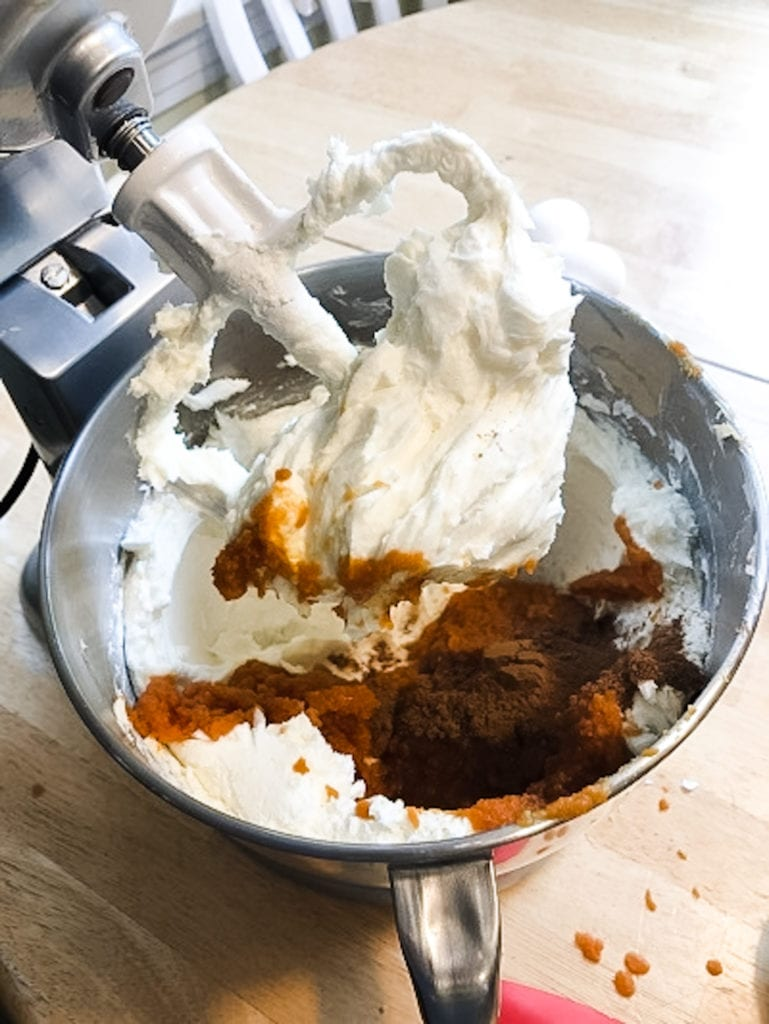spices being added to a bowl of batter with a mixer