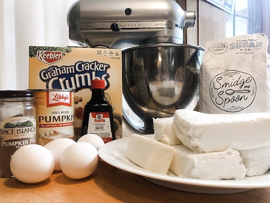 eggs, cream cheese, gram cracker crumbs, vanilla, pumpkin pie spice, and sugar in front of a mixer