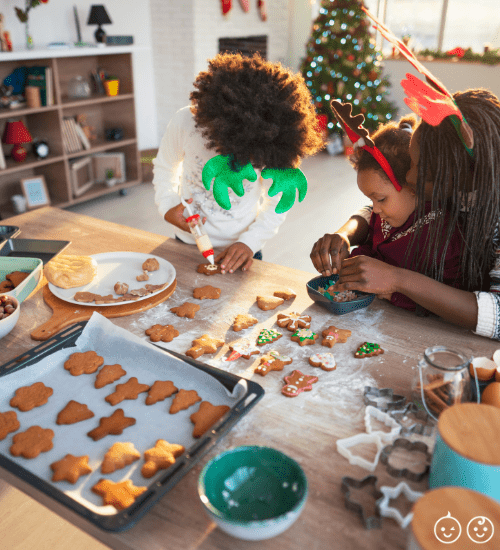 kids and mom decorating cookies during the holiday season