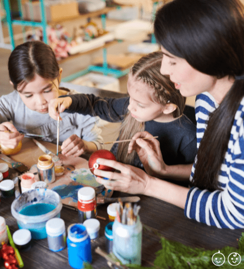 kids and mom painting Christmas ornaments at a table