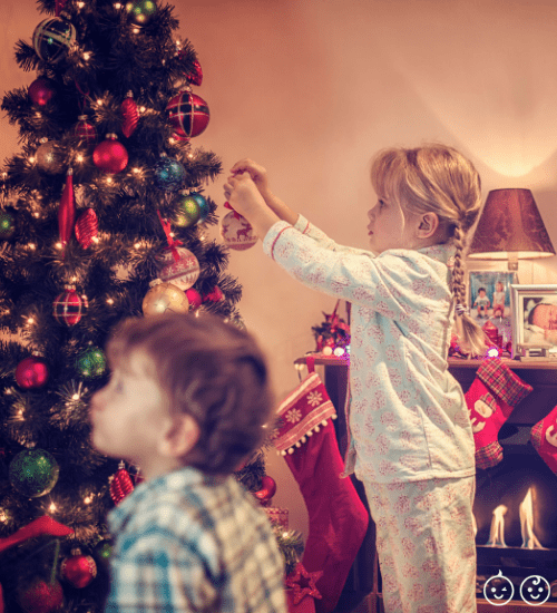 two young kids decorating a Christmas tree for the holiday season