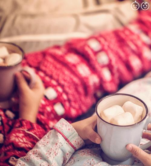 2 kids in holiday season pajamas holding hot chocolate with marshmallows