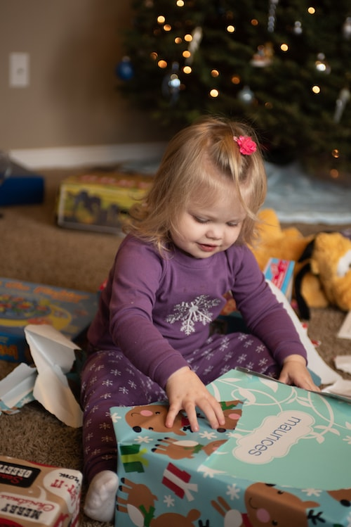 little girl opening presents in front of christmas tree 4 gift rule