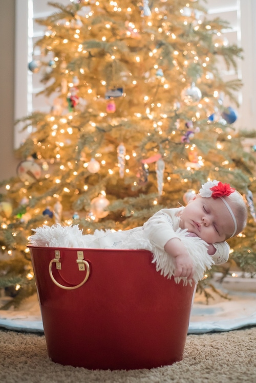 baby sleeping in a bucket set up in front of christmas tree 4 gifts rule