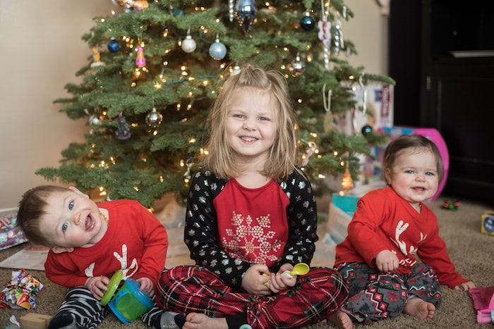 twins and older sister sitting in pajamas in front of christmas tree 4 gift rule