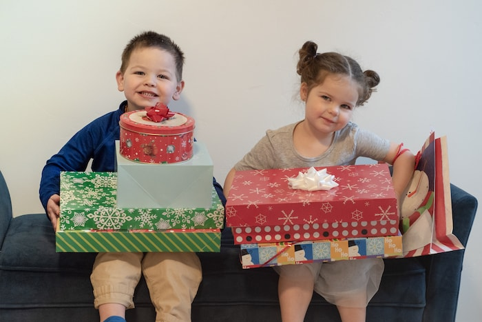 twin boy and girl holding a stack of gifts 4 gift rule
