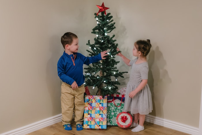 twin toddlers standing next to small christmas tree 4 gift rule