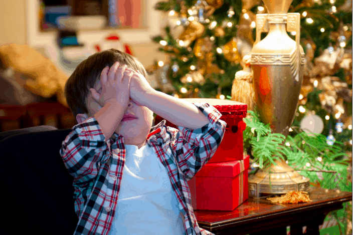 kids with hands over his eyes holiday stress