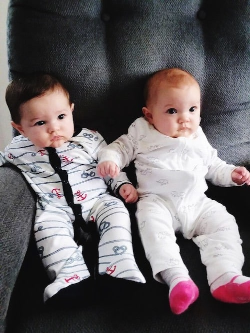 twin babies sitting on a couch maternity leave