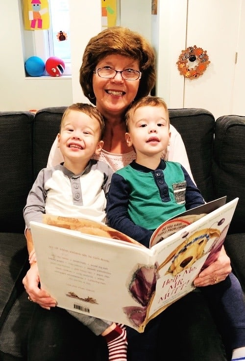 grandma holding twin boys in her lap while reading a book