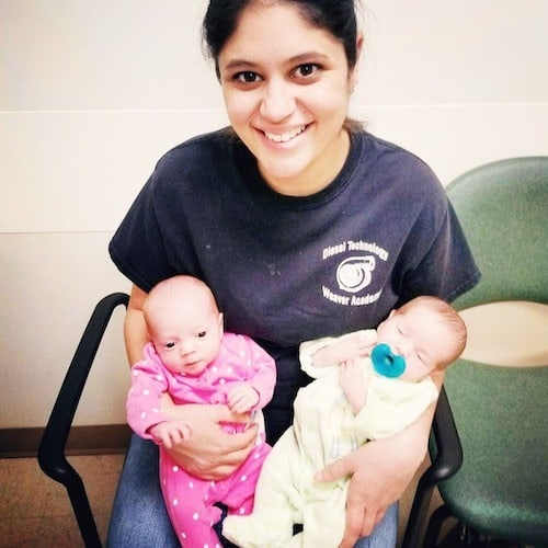 mom sitting in chair holding newborn twins hot mess mom