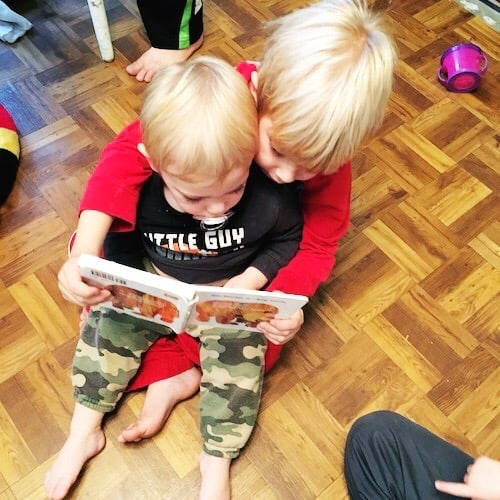 twin toddler boys sitting in each others laps reading a book kids to read