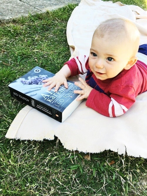 baby holding large book lying on blanket on the grass kids to read