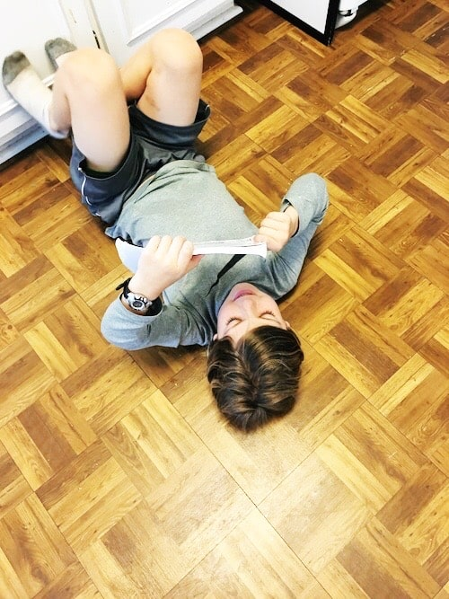 boy reading while laying on kitchen floor kids to read