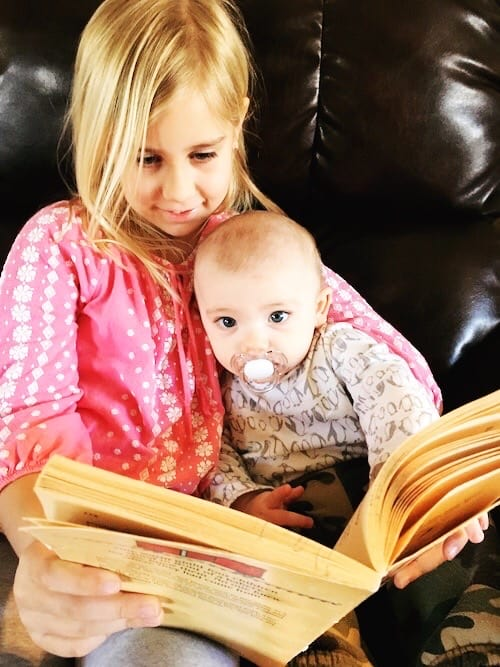 young girl holding a baby in her lap and reading a book kids to read