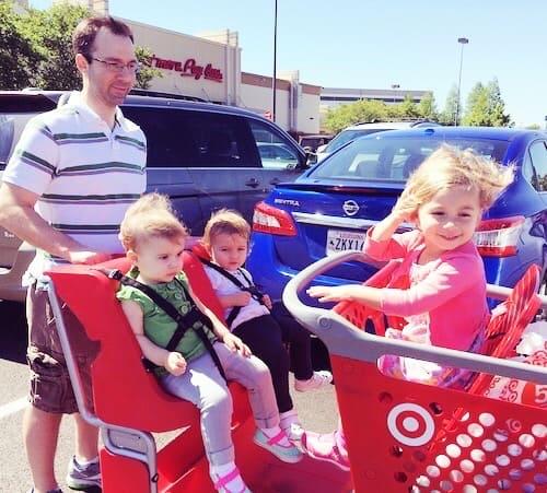 dad pushing little kids in a target shopping cart love language