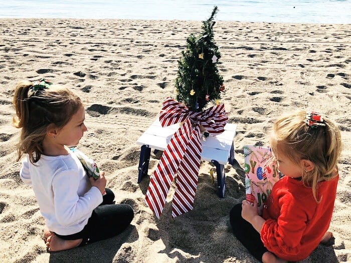 two young girls sitting on the beach with a tiny christmas tree new traditions