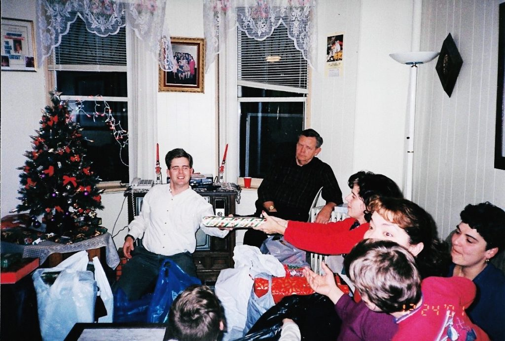 1980s photo of family passing gifts at christmas new traditions