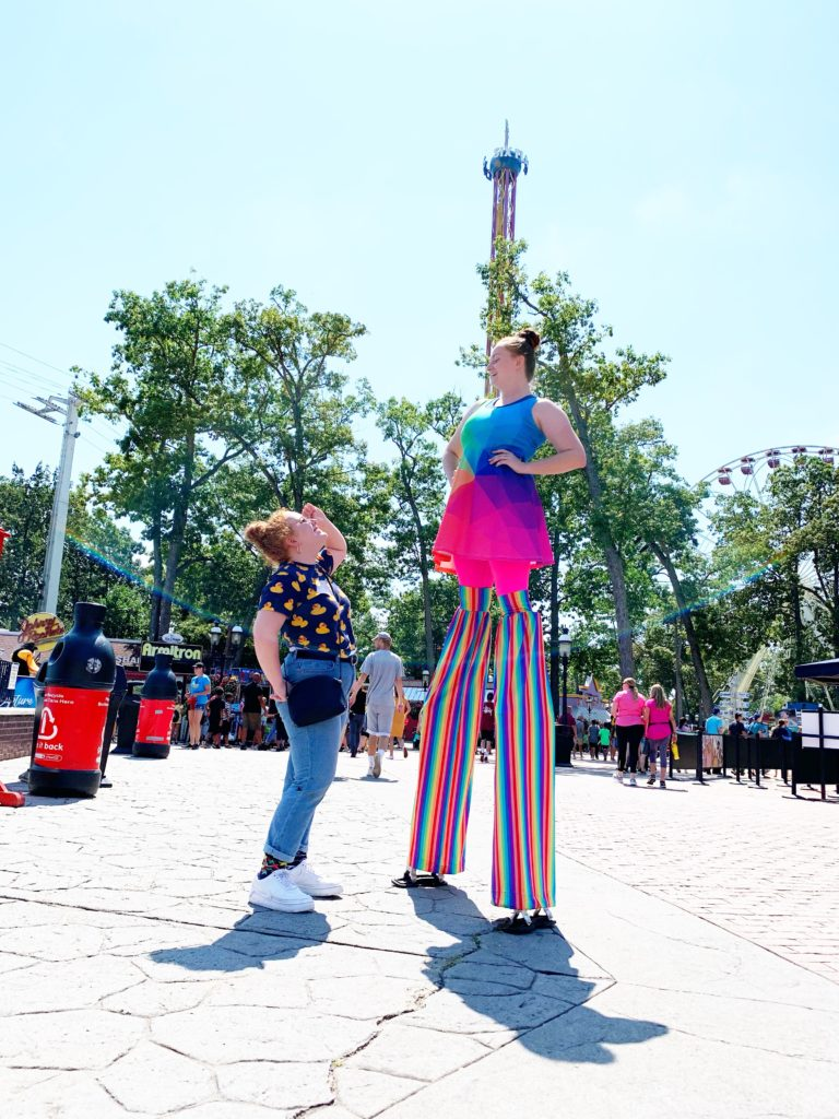 Girl standing by woman on stilts at Six Flags ticket prices