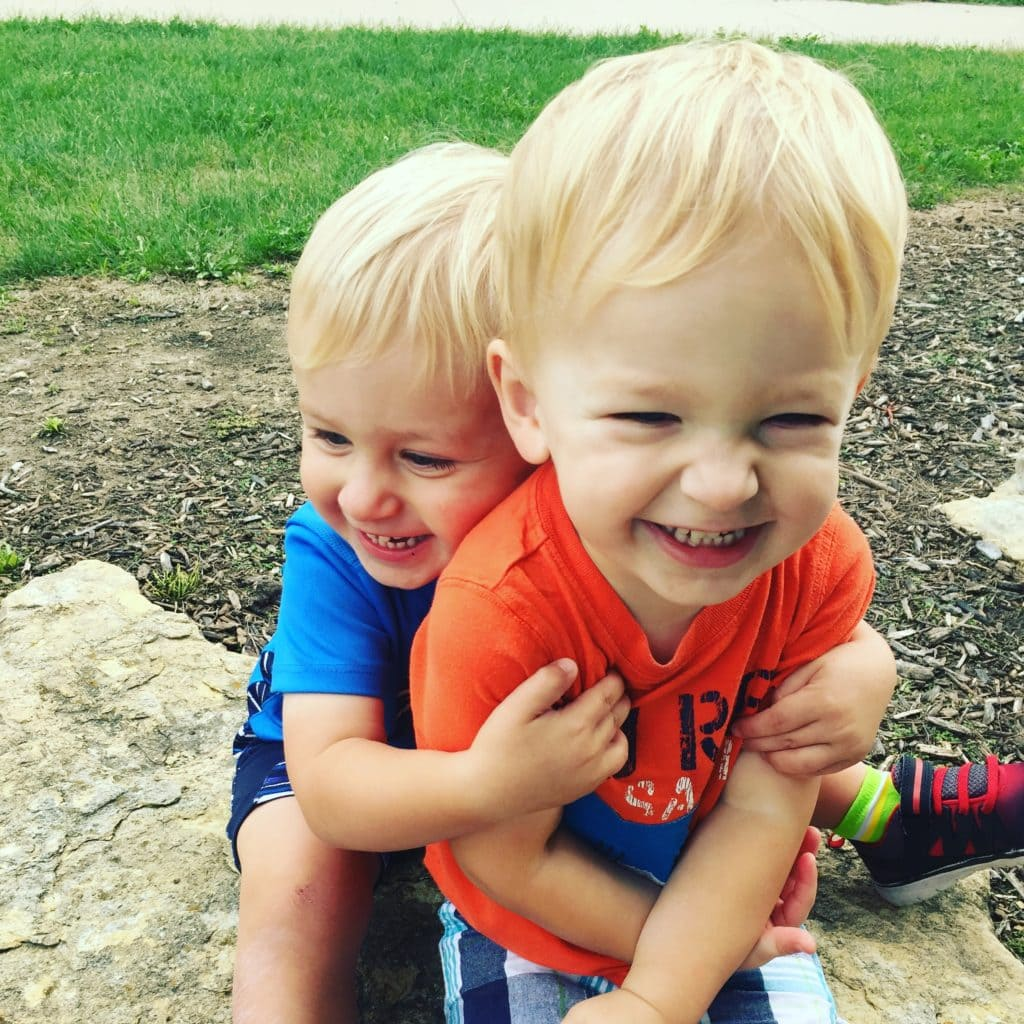 twin toddler boys hugging mother-in-law taught