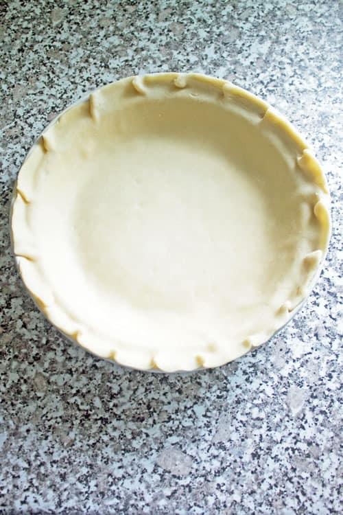 pressing crust into pie pan apple pie