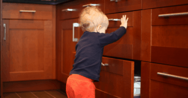 baby looking through kitchen drawers baby proofing