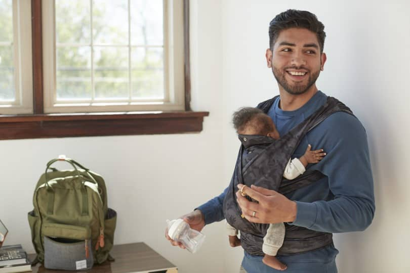 man wearing baby in baby carrier