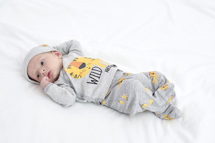 Buying Twin Clothes baby on a bed