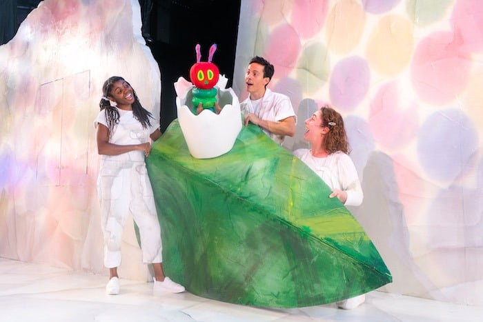 3 actors posing with caterpillar puppet the very hungry caterpillar