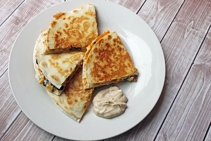 chipotle ranch chickne quesadilla on a plate with dipping sauce