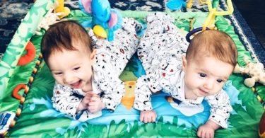 twin babies doing tummy time on a floor mat container baby syndrome