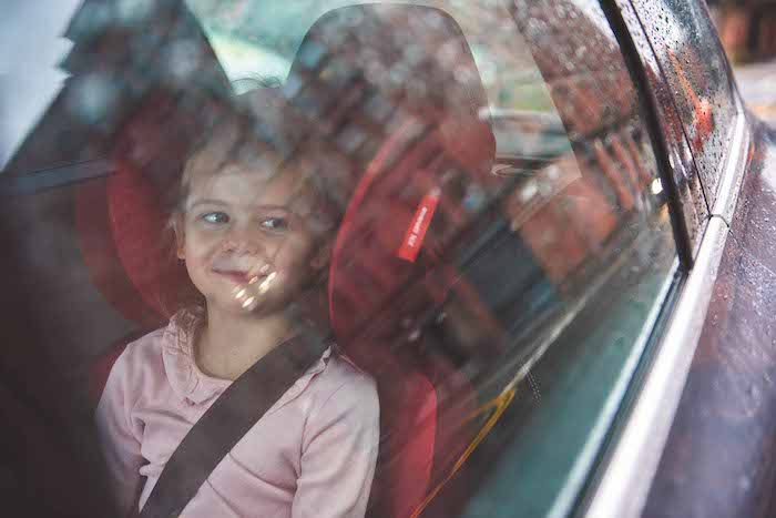 girl looking out car window in booster seat