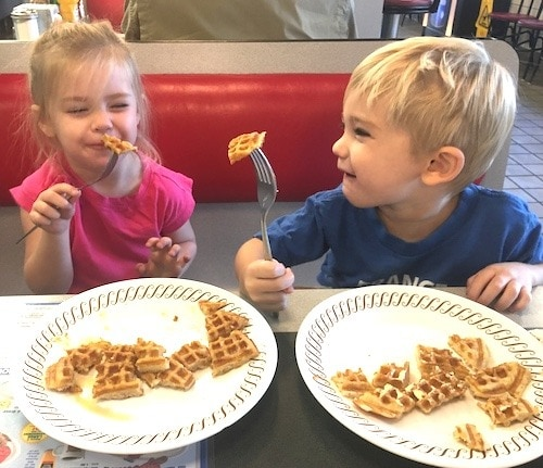 twin kids holding forks with waffles mama of newborn twins